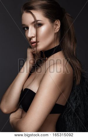 Beautiful woman with evening make-up and long straight hair . Smoky eyes. Fashion photo. Picture taken in the studio on a black background.