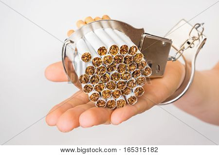 Female Hand With Handcuffs And Cigarettes On White