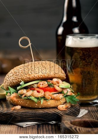 Burger with prawns grilling and a glass lager beer on a wooden table