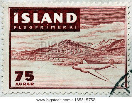 LUGA RUSSIA - NOVEMBER 6 2016: A stamp printed by ICELAND shows view of aircraft over Icelandic landscape circa 1947