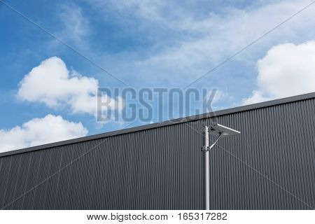 Warehouse buildings wall with electricity post, and blue sky with white cloud
