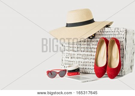 White wicker suitcase women's hat bracelets sunglasses e-book and red shoes