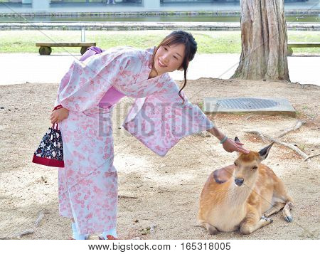 Nara, Japan - June 6,2016: Unidentified beautiful woman in Japanese traditional dress called Yukata play with deer at Nara Park. Nara Park is a large park in central Nara, home of freely roaming deer.