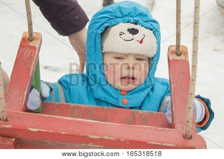 child wants to sit on the swings and crying very upset.