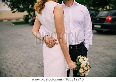 The bride and groom stand hugging outdoors