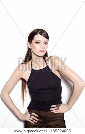 A brunette woman wearing a black top and gold pants on a white background