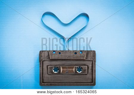 heart shape from cassette tape over paper background, top view