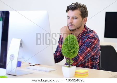Rear View Of A Businessman Analyzing Graph On Computer