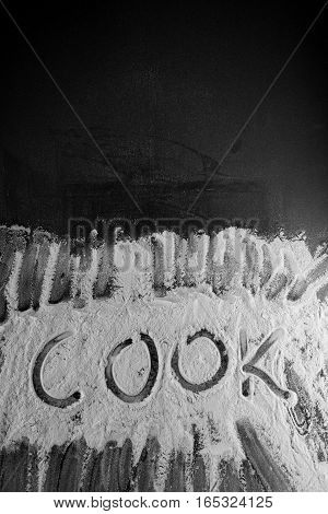 Word Cook Written In Flour On Table