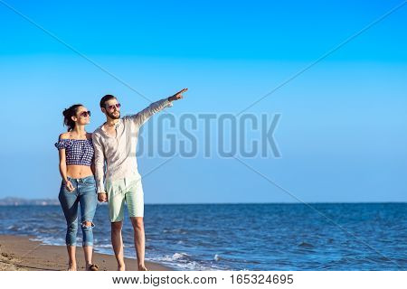 Couple walking on beach. Young happy interracial couple walking on beach smiling holding around each other. Latino woman, Caucasian man.
