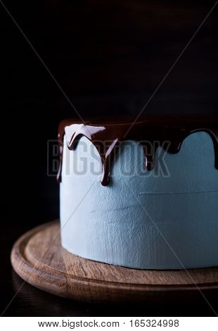 Blue souffle cake with chocolate icing on a dark wooden background
