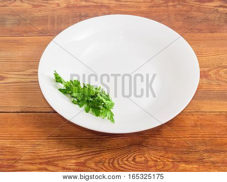 Background of a white dish with bunch of fresh parsley on the edge of a dish on an old wooden surface