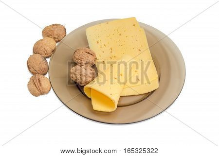 Several slices of a semi-hard cheese made with pounded walnuts on a glass dish and several whole walnuts on a light background