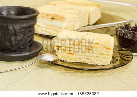 Piece of layered sponge cake on a glass saucer with spoon on the background of the rest of the cake black cup and jam closeup on a cloth surface
