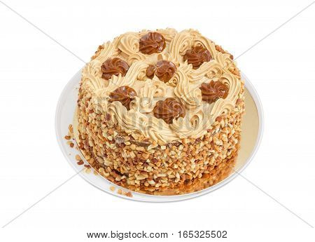 Round sponge cake decorated with butter cream and caramelized condensed milk sprinkled with grated nuts on a light background