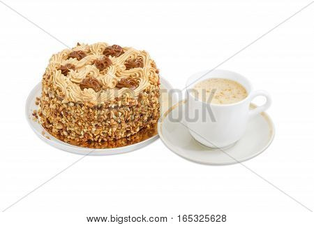 Round sponge cake decorated with butter cream and caramelized condensed milk sprinkled with grated nuts and coffee with cream in white cup on a light background