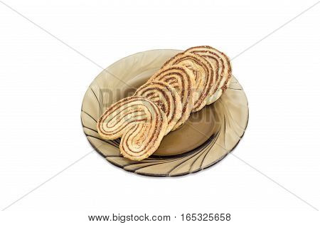 Several flaky cookies in a palm leaf shape made from puff pastry with chocolate filling on a glass saucer on a light background