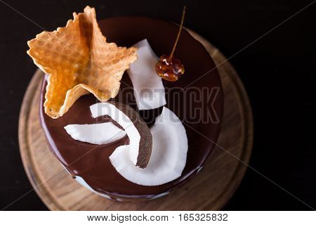 Top view of a chocolate cake decorated with waffles and caramel