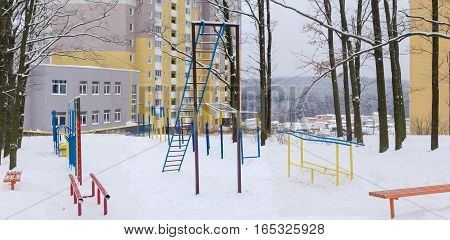 Panorama of outdoor gym in winter public park coverd snow on the background of modern multistory apartment complex