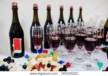 Red Champagne On Glasses Background Bottles On Reception.