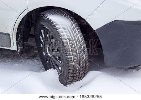 Front wheel of the white car with a snow tire covered partly mud and partly snow closeup during snowfall