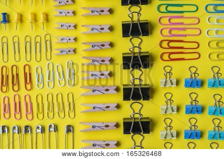 Pins and paper clips collection, yellow background
