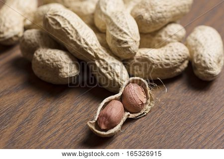 closeup peanuts on wooden background, healthy, seed