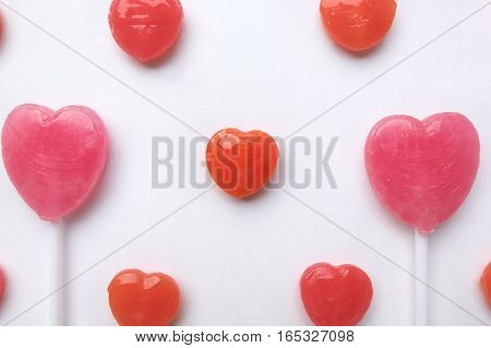 Pink Valentine's day heart shape lollipop with small red candy in cute pattern on empty white paper background. Love Concept. colorful hipster style. Knolling top view.