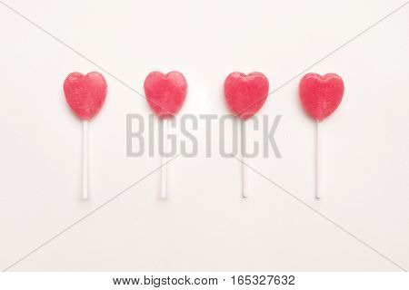 four Pink Valentine's day heart shape lollipop candy on empty white paper background. Love Concept. Knolling top view. Minimalism colorful hipster style.
