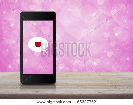 Love message on modern smartphone screen on wooden table over blur pink background Internet online connection Valentines day concept