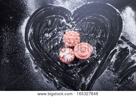 Pink cupcakes on a dark background with flour top view pink cream paste marmalade candies