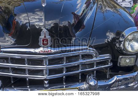 MOSCOW RUSSIA - OCTOBER 1 2016: Fragment of the front of the old Soviet car ZIM (GAZ-12) - the radiator grille headlight and logo on the hood.