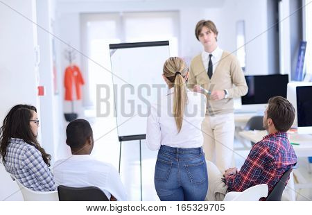 Businessman giving a presentation to his colleagues at work standing in front of a flipchart with notes and diagrams
