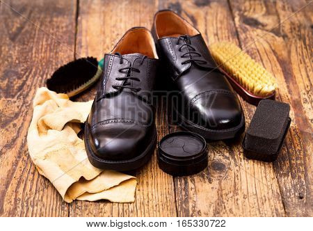 black men's shoes with care accessories on wooden background