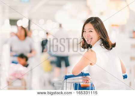 Smiling Asian woman with shopping cart or trolley at department store or shopping mall happy lifestyle or shopaholic concept blur bokeh background with crowd and copy space