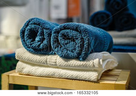 Four clean soft double bath towels set of different colors stacked, lying on wooden chair. Side view closeup
