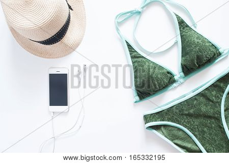 Set of beach items. Green bikini with mobile phone and hat on white background.