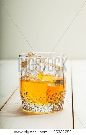 glass of whiskey with ice on a white wooden background