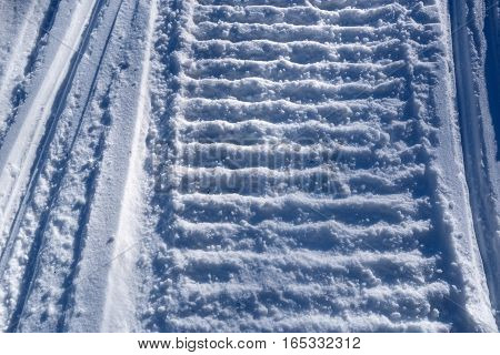 Close-up of a snowmobile track mark on the snow