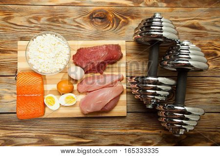 Protein diet, fish, cheese, eggs, meat, chicken and dumbbells on a wooden background