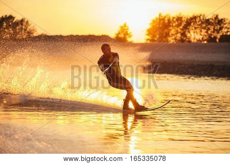 Outdoor shot of man water skiing at sunset . Man wakeboarding on a lake.