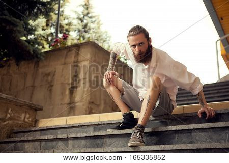 Beardead Tattooed Cool Looking Guy Sitting In Street On Stairs
