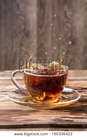 Picture of black tea spill in glass mug on wooden table