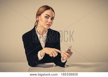 attractive dark-haired woman dressed in a black suit is sitting at a table in an office. Secretary looking at the camera and the phone dials the number