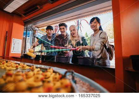 Group Of Friends Playing Fishing Game At Fairground