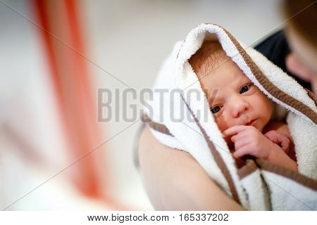 Mother holding her newborn baby daughter after birth on arms. Mum with baby girl, love. New born child cuddling in mama arms and looking at the camera. Bonding, family, new life