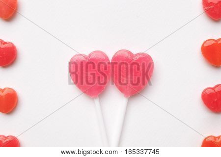 two Pink Valentine's day heart shape lollipop candy on empty white paper background. Love Concept. Knolling top view. Minimalism colorful hipster style.
