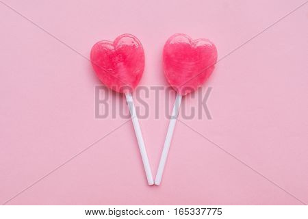 two Pink Valentine's day heart shape lollipop candy on empty pastel pink paper background. Love Concept. Knolling top view. Minimalism colorful hipster style.