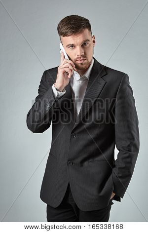 Portrait of a handsome businessman making a phone call against a grey background. Emotions. A man looks into the camera