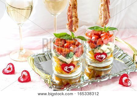 Festive verrines with grilled bacon on skewers. Original feed caprese salad in a glass. Serving for the holidays: Valentine's Day birthday Mother's Day. Selective focus